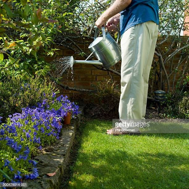 Senior man watering flower bed with watering can, low section