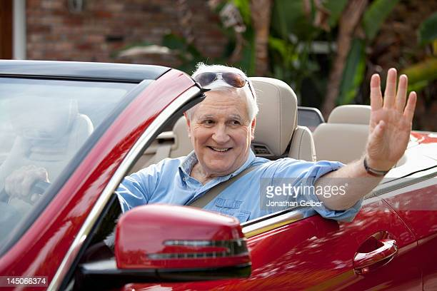 A senior man waving from driver's seat of convertible