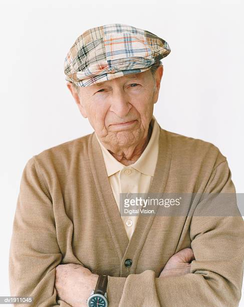 senior man wearing a flat cap standing with his arms crossed - flat cap stock pictures, royalty-free photos & images