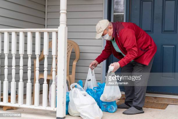 senior man wearing a protective mask and gloves is taking groceries out of the bins left on his porch into his house during covid-19 pandemic outbreak. - alex potemkin coronavirus stock pictures, royalty-free photos & images