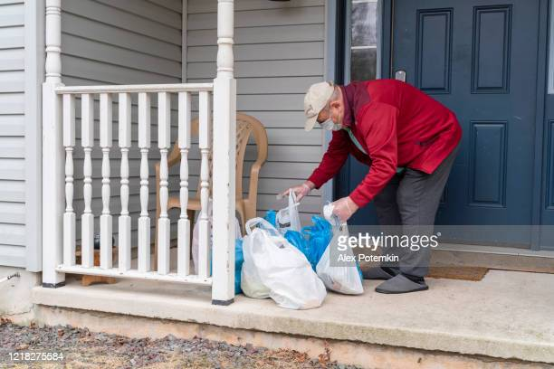 senior man wearing a protective mask and gloves is taking groceries left on his porch into his house during covid-19 pandemic outbreak. - alex potemkin coronavirus stock pictures, royalty-free photos & images