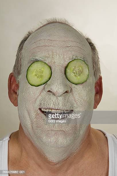 Senior man wearing beauty mask and cucumber slices over eyes, smiling
