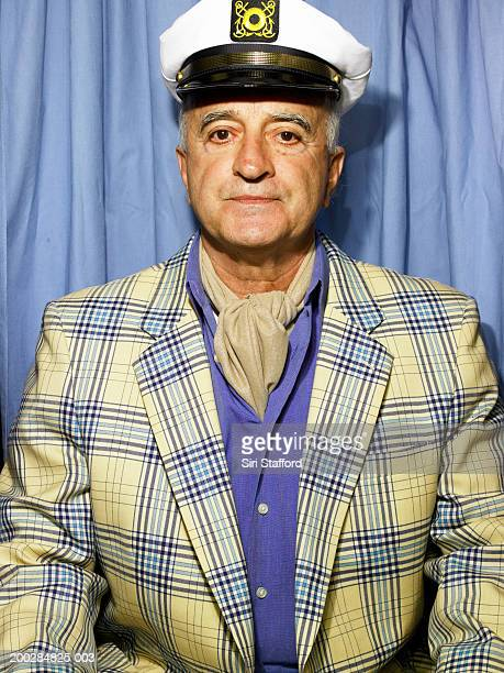 Senior man wearing blazer and cap in photo booth
