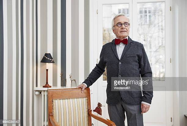 Senior man wearing bow tie at home