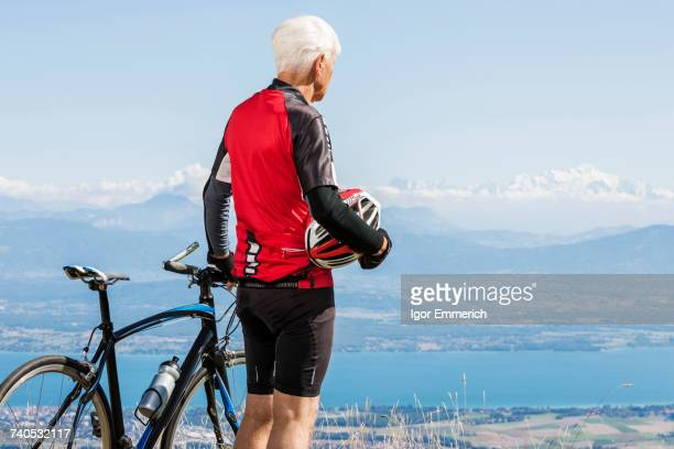 Senior man wearing cycling clothes, standing on hill, beside bicycle, looking at view, Geneva, Switzerland, Europe