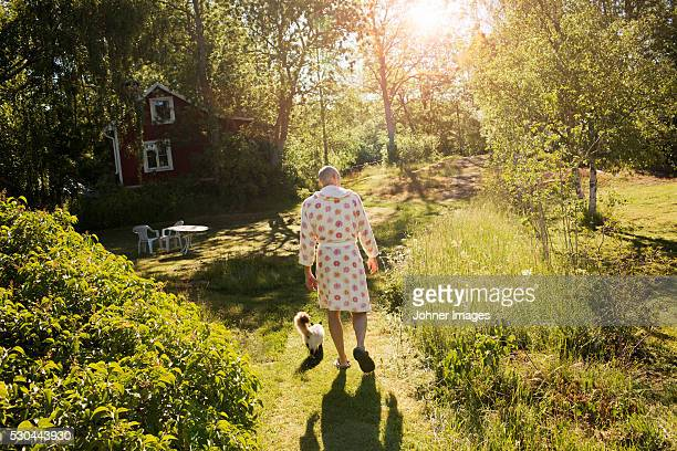 senior man wearing dressing gown walking in garden with cat - bathrobe stock pictures, royalty-free photos & images