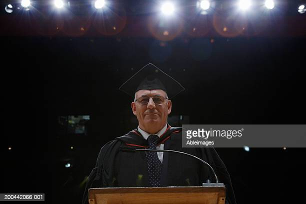 Senior man wearing graduation gown standing at lectern, portrait