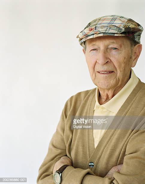senior man wearing hat, arms crossed, smiling, portrait - flat cap stock pictures, royalty-free photos & images