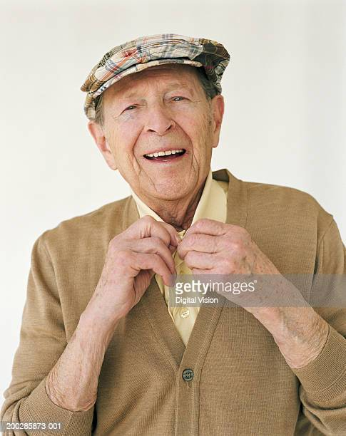 Senior man wearing hat, doing up shirt button, smiling, portrait