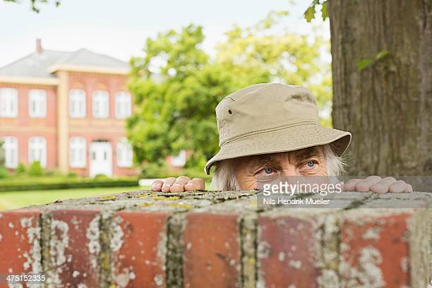 Senior man wearing hat peering over garden wall