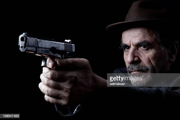Senior man wearing hat with gray facial hair aiming gun