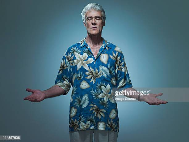 Senior man wearing hawaiian shirt posing as Jesus, portrait