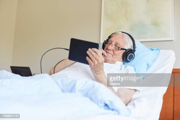 Senior man wearing headphones while using digital tablet on bed in hospital ward