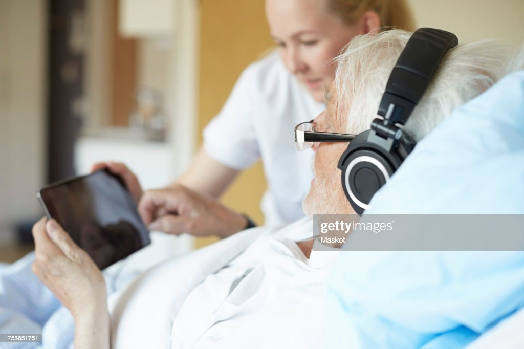 Senior man wearing headphones while using digital tablet with female nurse on hospital bed : Stock Photo
