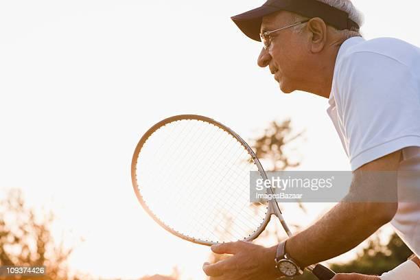 Senior man wearing holding tennis racquet at sunset