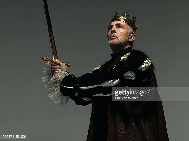 senior man wearing king costume, and holding sword while looking away - king royal person stock pictures, royalty-free photos & images