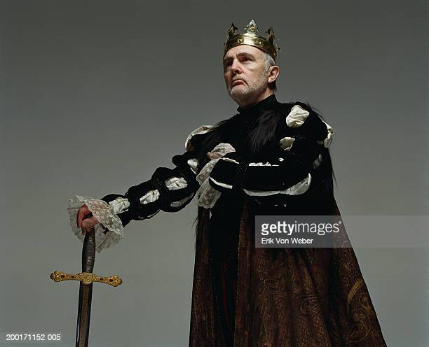 senior man  wearing king costume with sword, and looking away - koning koninklijk persoon stockfoto's en -beelden