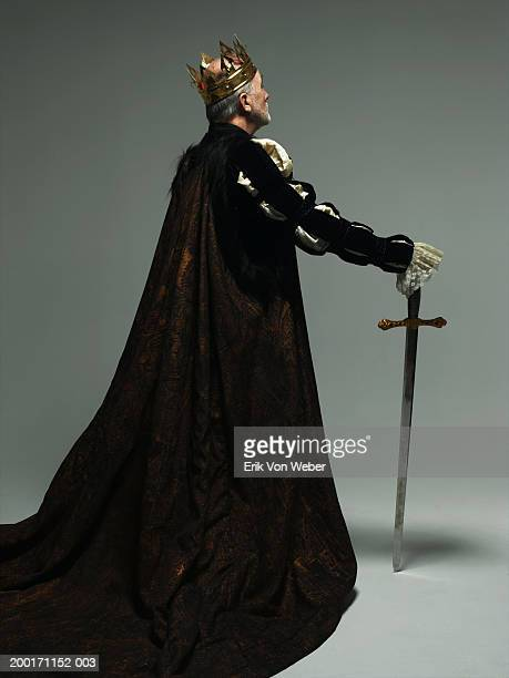 Senior man wearing king costume with sword, rear view
