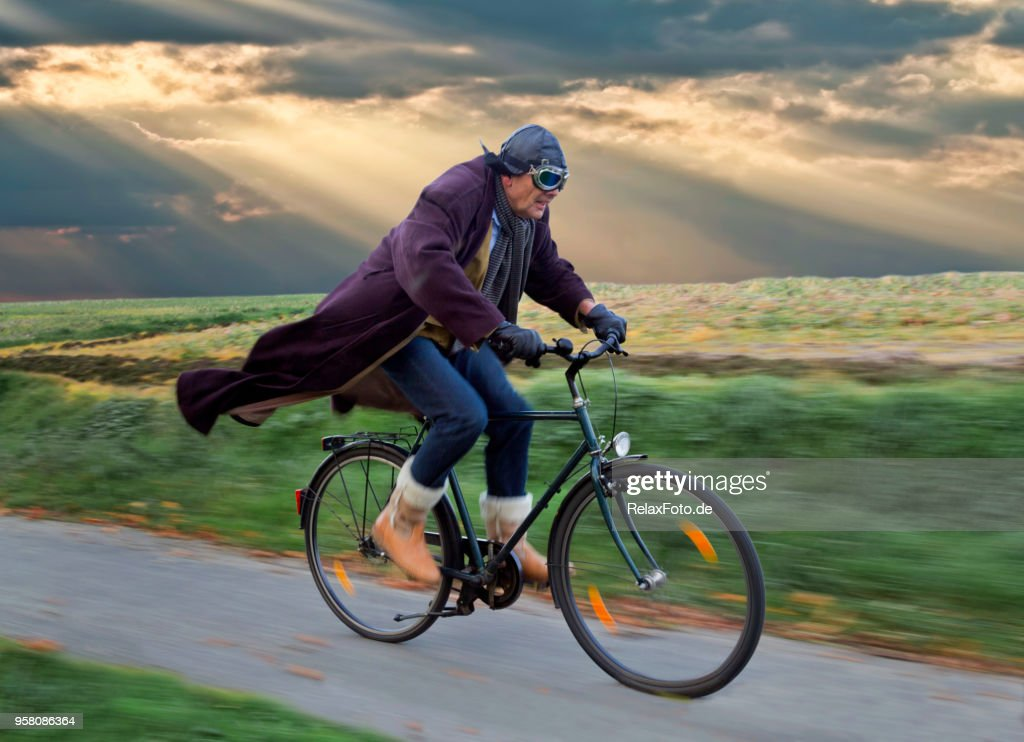Senior man wearing leather helmet and retro aviator glasses cycling with blowing coat under dramatic skyscape : Stock Photo