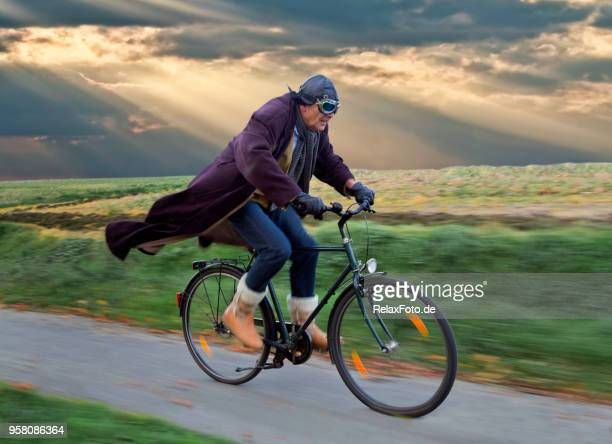 senior homme cuir rétro et casque aviator lunettes de cyclisme avec soufflage manteau sous skyscape dramatique - velo humour photos et images de collection