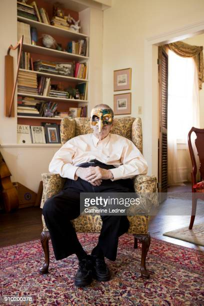 Senior Man wearing Mardi Gras Mask Seated in Wing backed chair