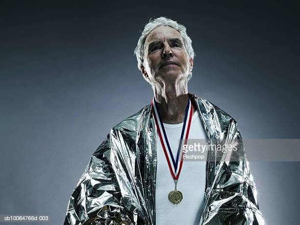 Senior man wearing medal and foil blanket, studio shot