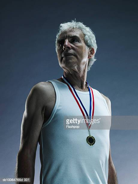 Senior man wearing medal, studio shot