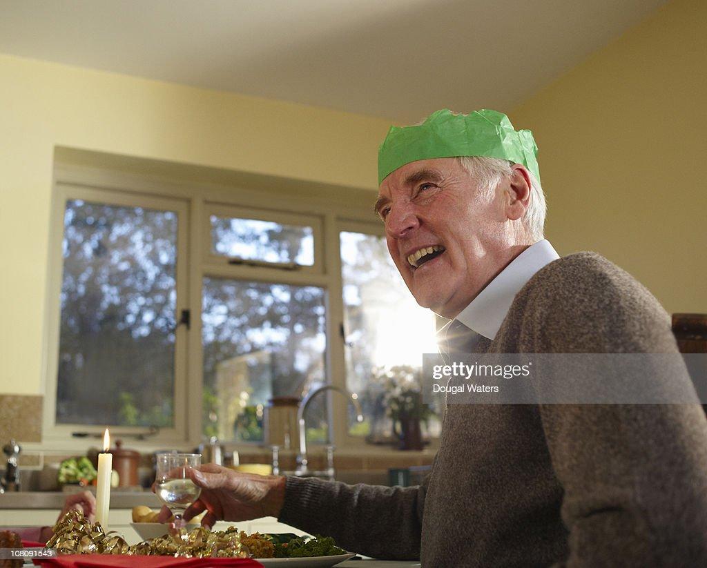 Senior man wearing party hat in kitchen. : Stock Photo
