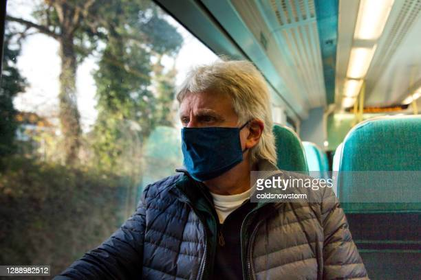 senior man wearing protective face mask in train carriage - carriage stock pictures, royalty-free photos & images