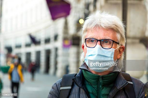 senior man wearing protective face mask on city street - fragility stock pictures, royalty-free photos & images