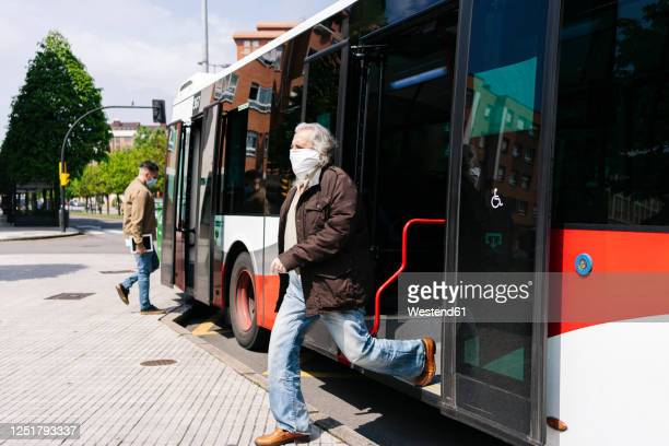senior man wearing protective mask getting off public bus, spain - entrar imagens e fotografias de stock