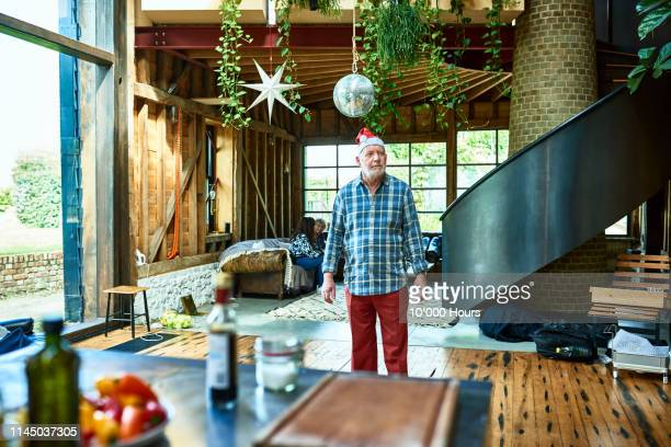 senior man wearing santa hat standing in middle of room - grumpy old man stock pictures, royalty-free photos & images