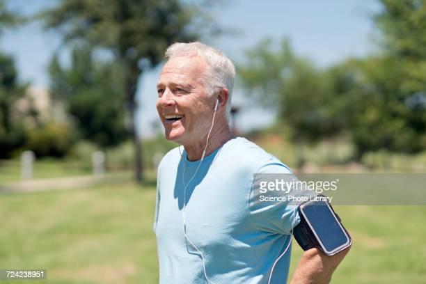 senior man wearing smartphone and earphones - armband stock-fotos und bilder