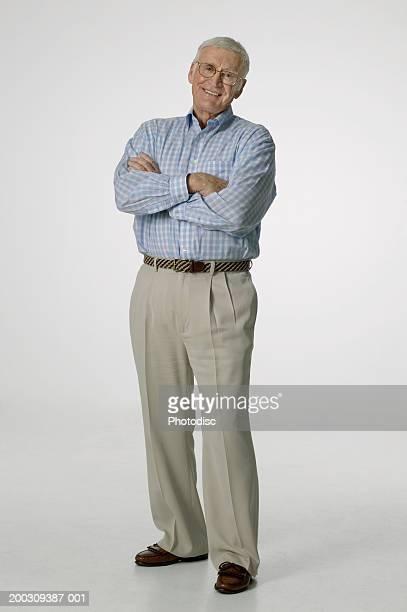 Senior man wearing spectacles, posing in studio, portrait