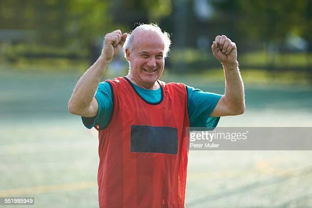 Senior man wearing sports bib cheering
