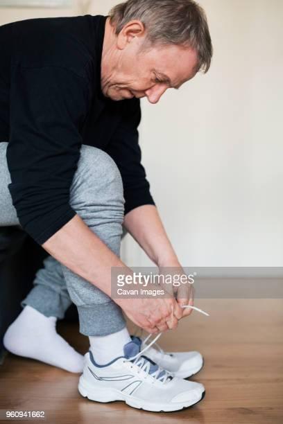 Senior man wearing sports shoes at home