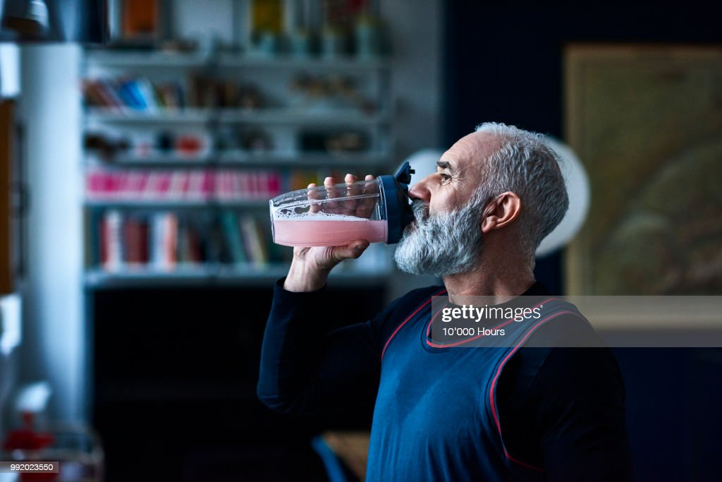 Senior man wearing sports top gulping health drink from container : Foto de stock