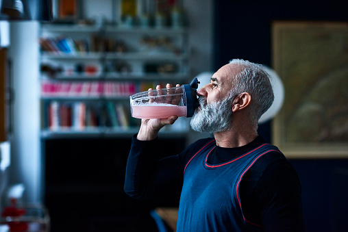 Senior man wearing sports top gulping health drink from container - gettyimageskorea