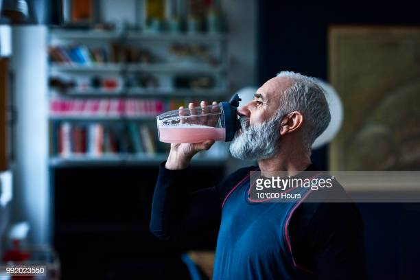 senior man wearing sports top gulping health drink from container - squash sport stock pictures, royalty-free photos & images