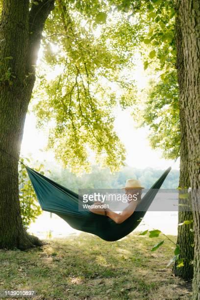senior man wearing straw hat relaxing in hammock at lakeshore reading book - seeufer stock-fotos und bilder