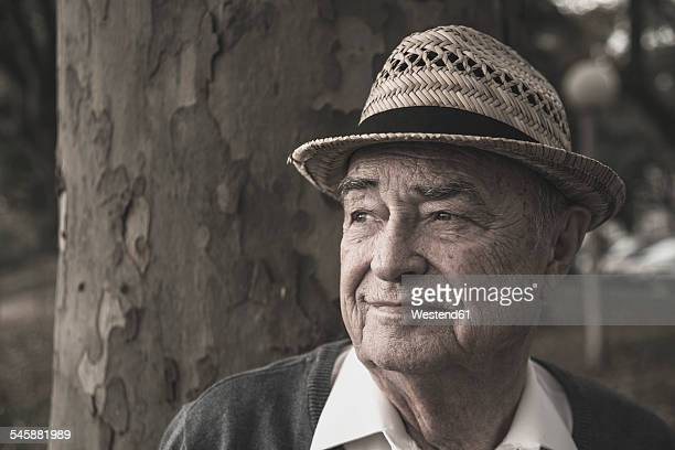 Senior man wearing straw hat thinking
