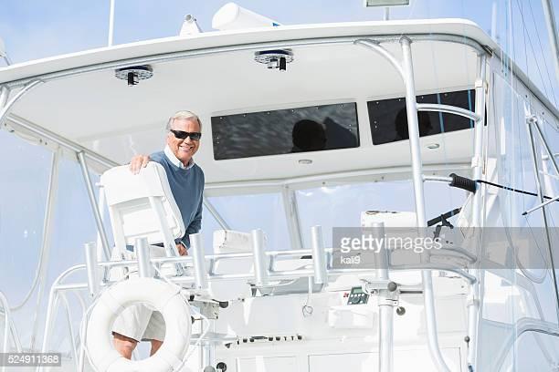 Senior man wearing sunglasses on his boat
