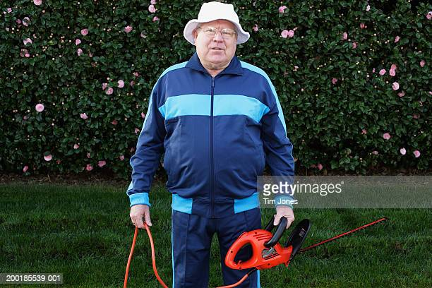 Senior man wearing tracksuit, holding hedge clippers, portrait