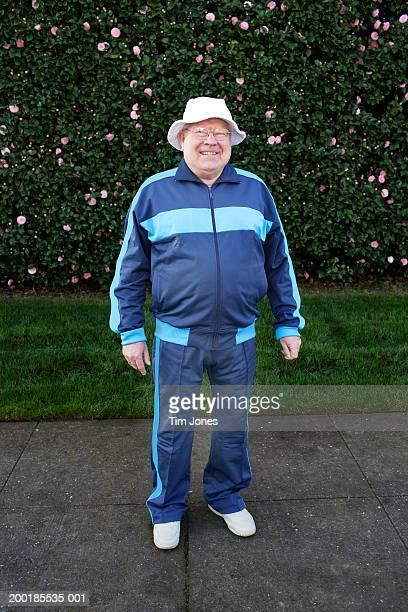 senior man wearing tracksuit, standing in front of hedge, portrait - trainingsanzug stock-fotos und bilder
