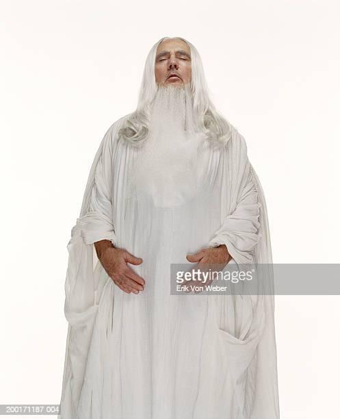 senior man wearing white robe with eyes closed - 儀式用のローブ ストックフォトと画像