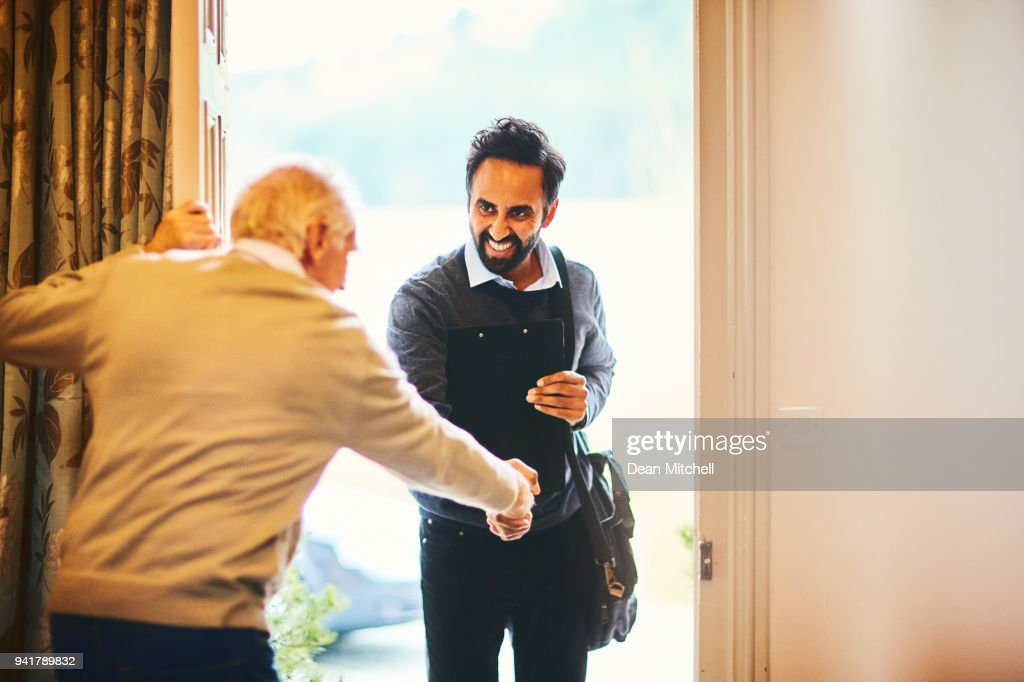 Senior man welcoming a healthcare worker - Home visit : Stock Photo