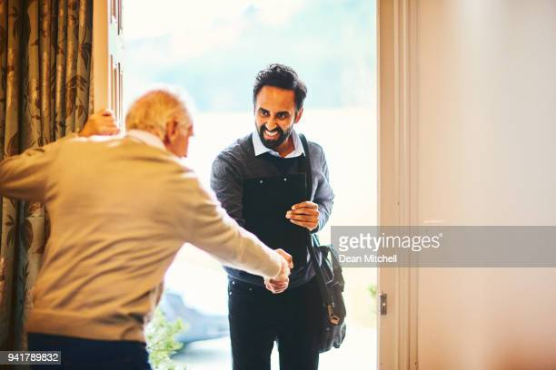 senior man welcoming a healthcare worker - home visit - visita imagens e fotografias de stock