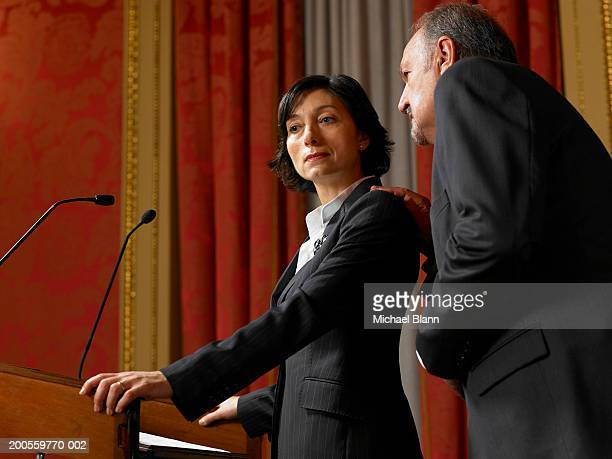 Senior man whispering to politician woman standing at lectern