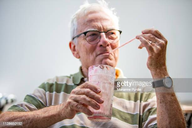 a senior man with a cold drink - milkshake stock pictures, royalty-free photos & images