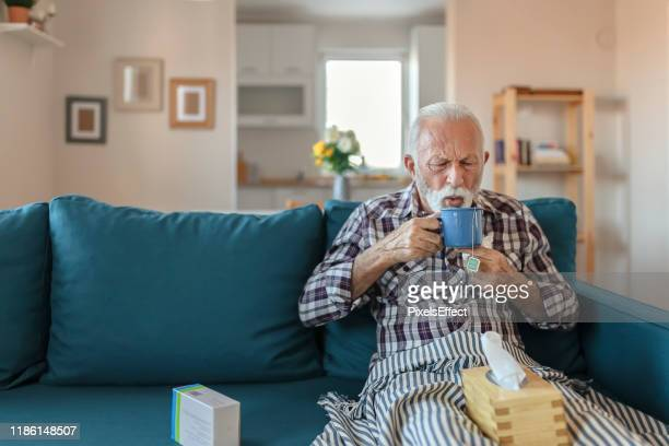 senior man with a cold drinking tea - coughing stock pictures, royalty-free photos & images